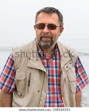 Peaceful carefree elderly man on the sea background - stock photo