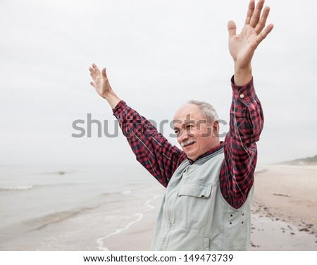 peaceful carefree older man with outstretched arms the coast at foggy day - stock photo