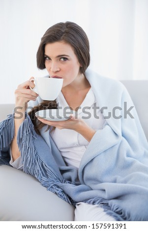 Peaceful casual brown haired woman in white pajamas drinking coffee in a bright living room - stock photo