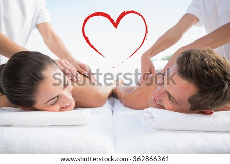 Peaceful couple enjoying couples massage poolside against heart - stock photo
