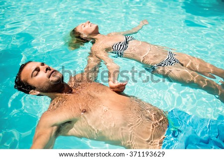 Peaceful couple floating in the pool with closed eyes - stock photo