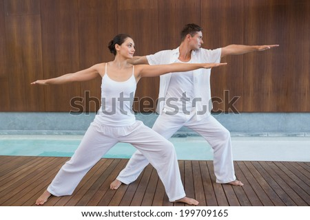 Peaceful couple in white doing yoga together in warrior position in health spa - stock photo