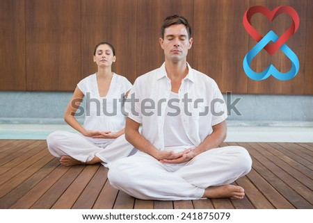 Peaceful couple in white sitting in lotus pose together against linking hearts - stock photo