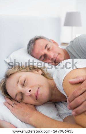 Peaceful couple sleeping and spooning in bed in bedroom at home - stock photo