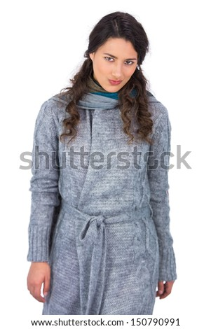 Peaceful curly haired model with winter clothes posing on white background