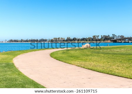 Peaceful curved paved pathway cuts through green grassy area along the river. Stone bench, person in small boat moving through the water in the background. Leisure and relaxation concept.   - stock photo