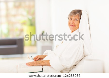 peaceful elderly woman reading book on bed - stock photo