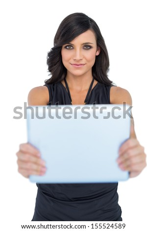 Peaceful elegant brown haired model holding tablet in front of her on white background