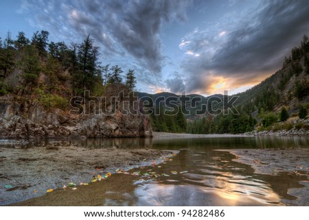 Peaceful evening at a mountain creek bend with sunset reflection - stock photo