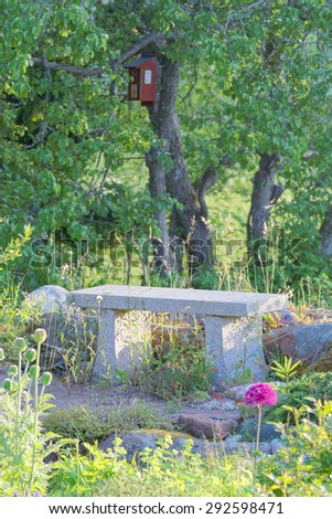 Peaceful feeling with a garden bench made of stone (granite) in the center of garden flowers in the morning light - stock photo