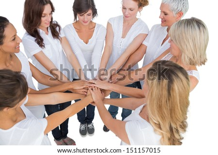 Peaceful female models joining hands in a circle on white background - stock photo