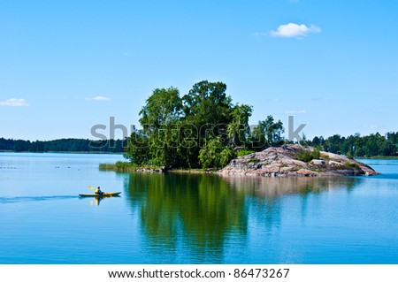 peaceful finnish scenery in Helsinki with a canoe in the distance - stock photo