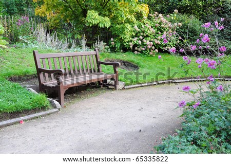 Peaceful Garden Scene with a Gravel Walkway and Wooden Bench - stock photo