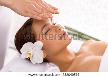 Peaceful girl getting reiki therapy - stock photo