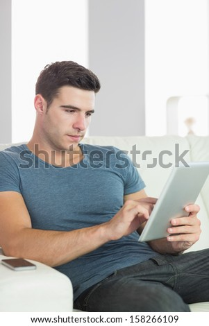 Peaceful handsome man relaxing on couch using tablet in bright living room