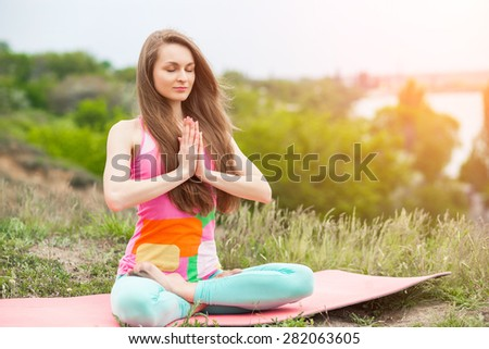 Peaceful healthy & fit young woman meditating on the nature with eyes closed - stock photo
