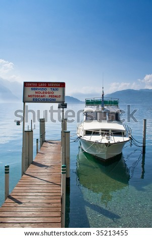 peaceful lake como with boat berth by the quay. this photo expresses the tranquility and unspoilt nature of lake como, Italy. - stock photo