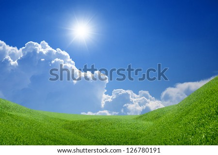Peaceful landscape - green grass field, bright sun, blue sky, white clouds - heaven on earth - stock photo