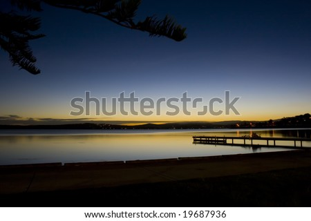 Peaceful long exposure overlooking calm water and a pier with children and bicycles. - stock photo