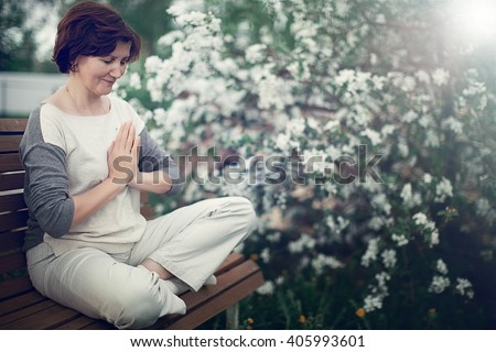 peaceful middle-aged woman meditating in the garden with her palms in namaste - stock photo