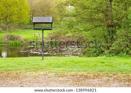 peaceful nature area with lake and bird table - stock photo