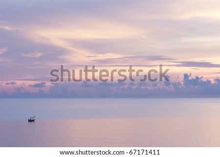 peaceful ocean at sunrise with a small boat - stock photo