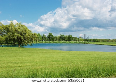 Peaceful Pond Scene.  A brilliant blue sky and massive fluffy white cumulus clouds are reflected in a farm pond that is surrounded by manicured green grass and bordered by a stand of shade trees - stock photo