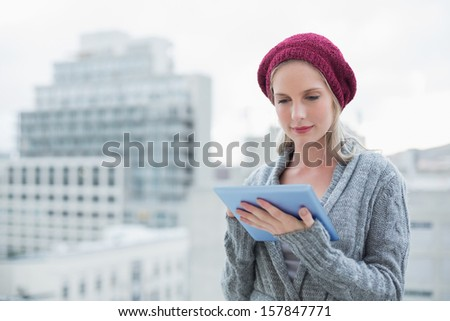 Peaceful pretty blonde using tablet pc outdoors on urban background - stock photo