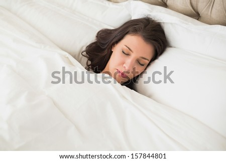 Peaceful pretty brown haired woman sleeping in her bed in a bright bedroom