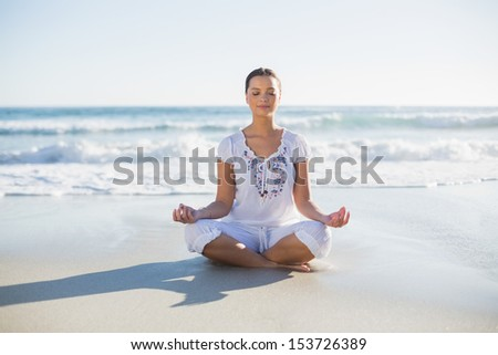 Peaceful pretty woman in lotus position on the beach on a sunny day - stock photo