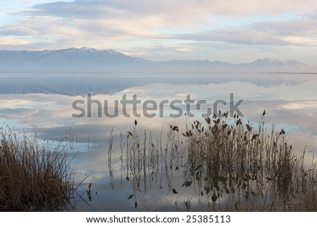 Peaceful reflection on a lake at sunset - stock photo