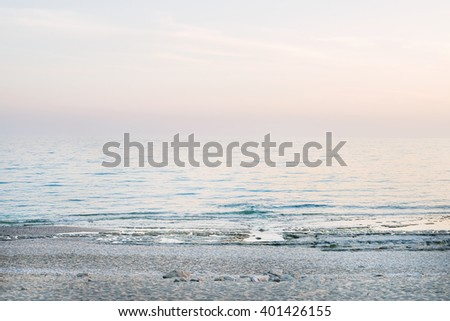 Peaceful scene of a calm sea at sunset, pastel colors - stock photo