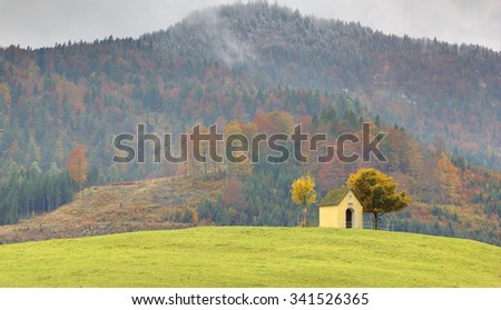 Peaceful scenery of a chapel on autumn hilltop with mountains in the background - stock photo