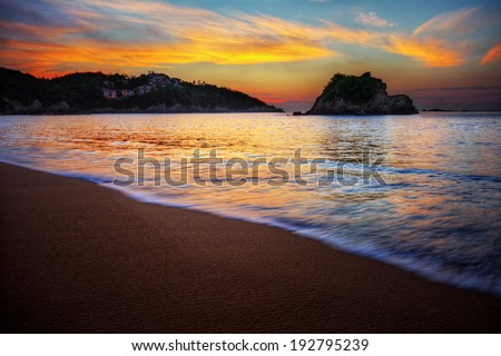 Peaceful sea bay sunrise over a sandy beach with orange clouds and distant cliffs - stock photo