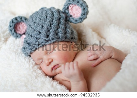 Peaceful sleeping newborn baby in a grey mouse hat - stock photo