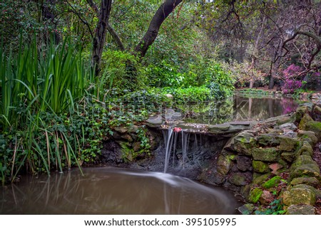 Peaceful stream and waterfall in spring with foliage and blooming trees.