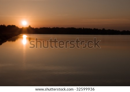 Peaceful Sunrise.  The rising sun is just above the horizon and is reflected in the calm waters of a reservoir