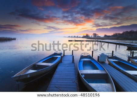 Peaceful sunrise with dramatic sky and boats and a jetty - stock photo