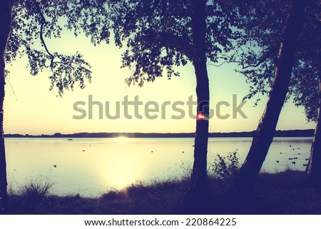 Peaceful Sunset at the Lakeshore with a retro vintage instagram filter effect - stock photo