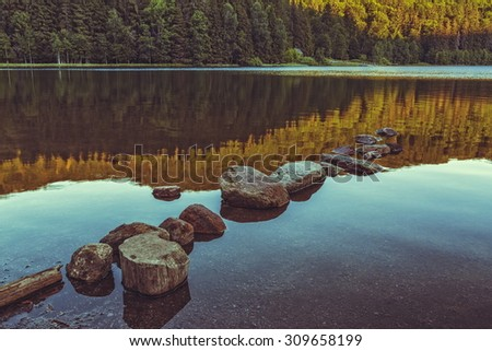 Peaceful sunset landscape with row of sunken rocks and reflections on the calm water surface of the Saint Ana (Sfanta Ana) lake, Romania. Toned colors. - stock photo