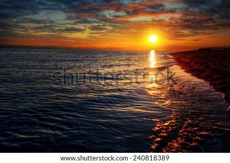 Peaceful sunset over sandy beach ocean shore - stock photo