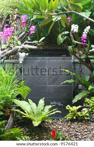 Peaceful waterfall fountain in a serene garden, good for feng shui! - stock photo