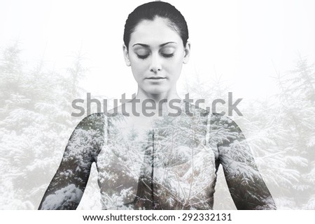 Peaceful woman in white sitting in lotus pose against snowy forest - stock photo