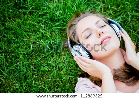 Peaceful woman listening to music with headphones outdoors - stock photo