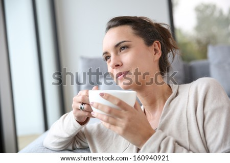 Peaceful woman relaxing at home with cup of tea - stock photo