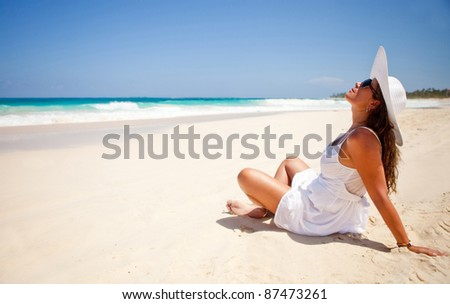 Peaceful woman sitting at the beach enjoying the ocean and relaxing - stock photo