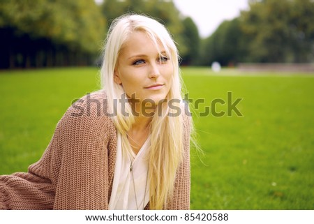 Peaceful woman sitting in a park and relaxing. - stock photo