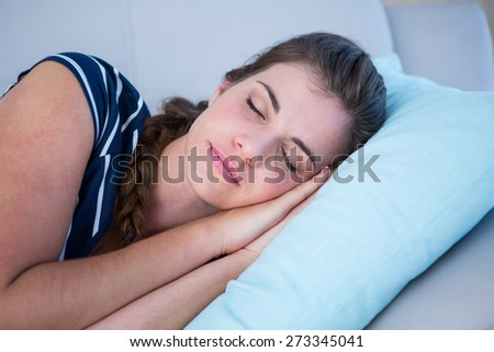 Peaceful woman sleeping on couch at home in the living room