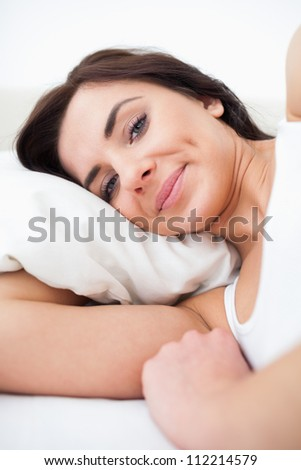 Peaceful woman waking up while lying in her bed in her bright bedroom - stock photo