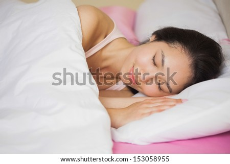 Peaceful young asian woman sleeping in her bed at home in bedroom - stock photo